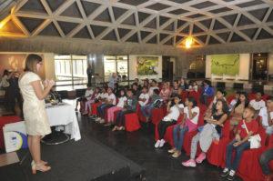crianças sentadas escutam professora falando em auditório